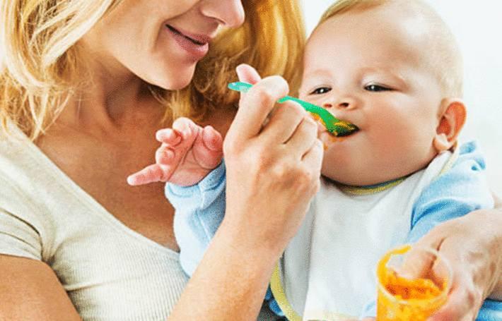 une maman donne de la purée de carotte à son bébé