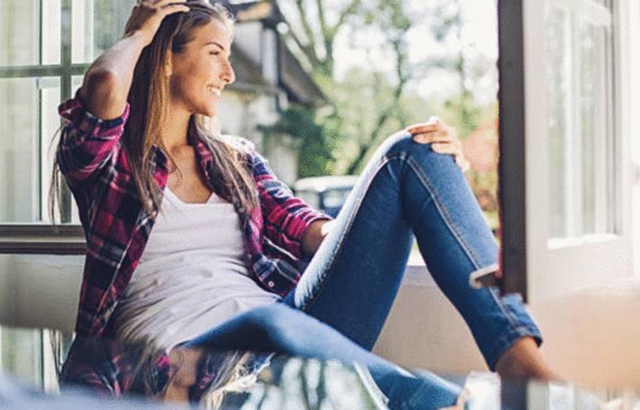 une femme assise ravie d'avoir transformer des produits courants en détachants efficaces
