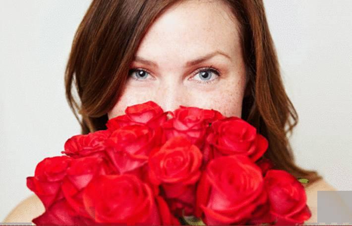 une femme respire un bouquet de rose rouge