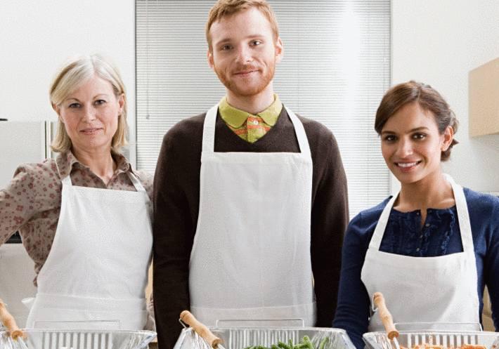 Un cuisinier, entouré de 2 cuisinières ont des tabliers blancs impeccables