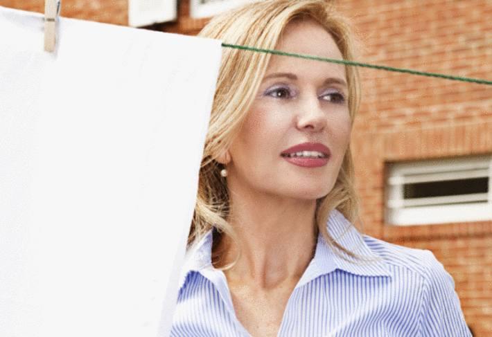 une femme blonde est devant un drap qui sèche accroché à un fil