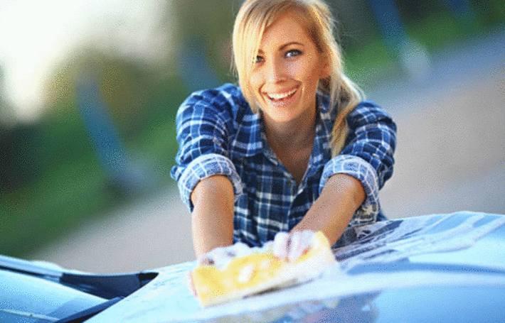 une femme enleve des taches sur sa voiture