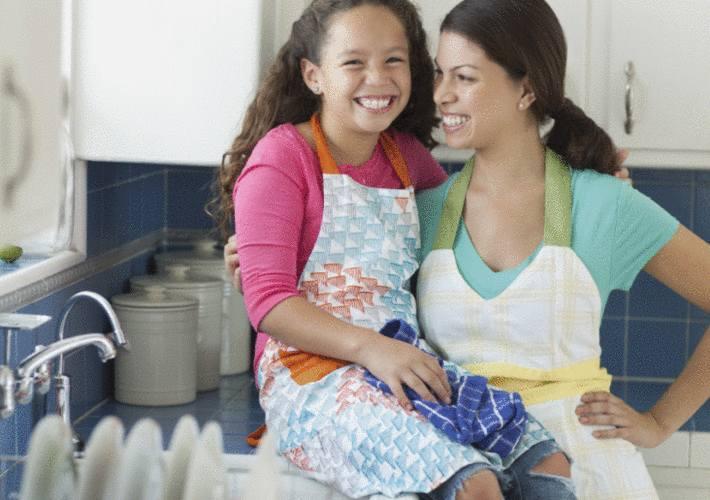 une maman et sa fille font la vaisselle