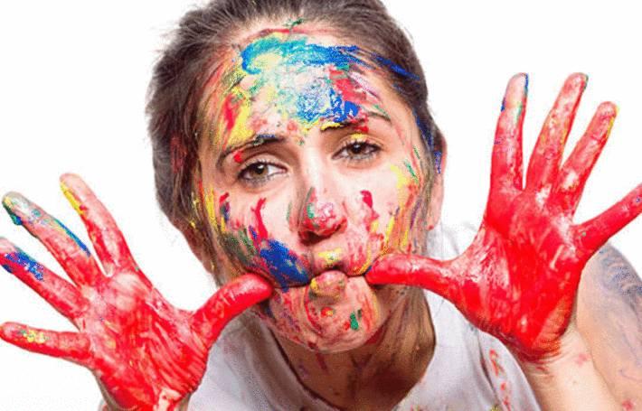 une femme couverte de taches de peinture sur le visage, les bras et les mains
