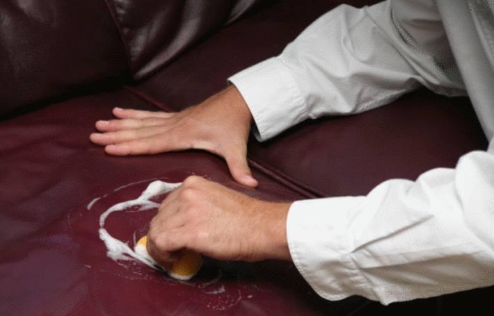 un bras d'homme en chemise blanche enlève une tache sur un canapé en cuir
