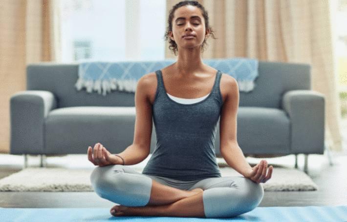une femme assise sur un tapis dans son salon pratique la meditation