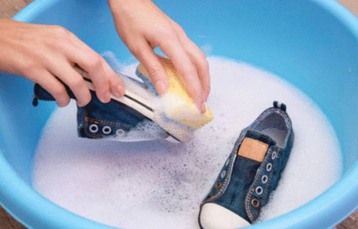 une personne lave des baskets dans une bassine
