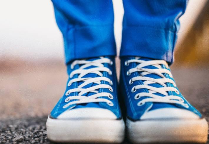 des baskets bleues, comme le pantalon, avec des semelles blanches