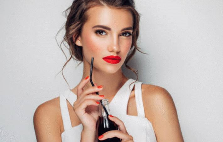 une femme boit du coca cola