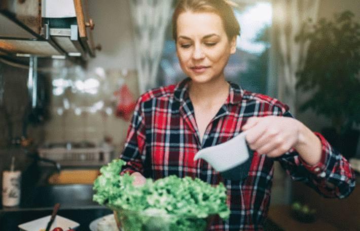 une femme verse de la vinaigrette dans un saladier de salade