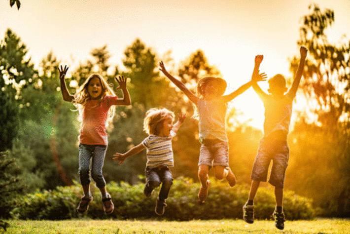 enfants-qui-sautent-au-parc-garçons-et-filles-chantant-au-parc
