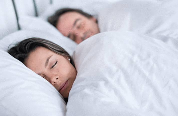 femme et homme cote-a-cote-endormi-sous-deux-couettes-blanches
