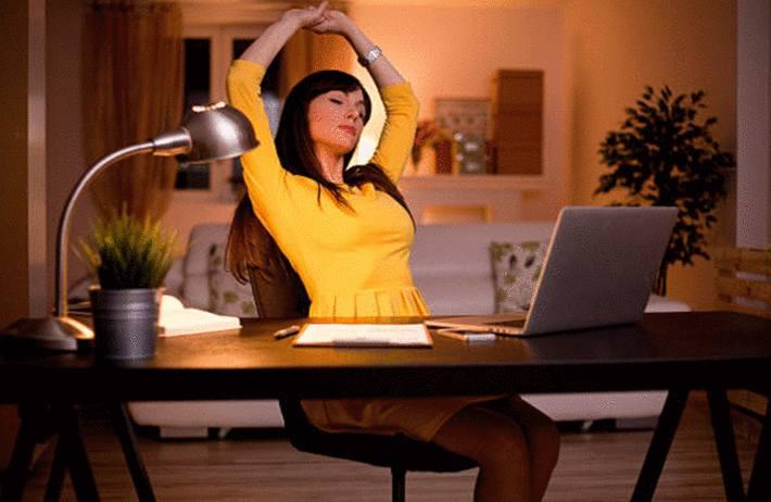 femme-brune-avec-une-robe-jaune-aux-cheveux-longs-setirant-devant-son-ordinateur-sur-son-bureau-avec-une-lampe-allumee-devant-un-canape-blanc
