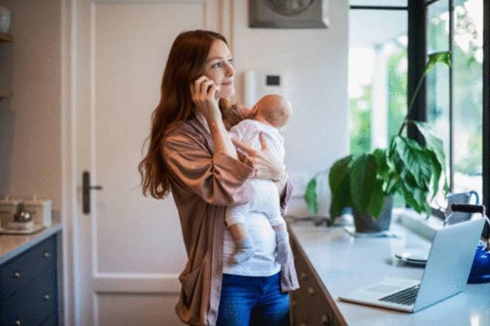 femme-brune-souriant-avec-son-nouveau-né-dans-sa-cuisine-propre-blanche