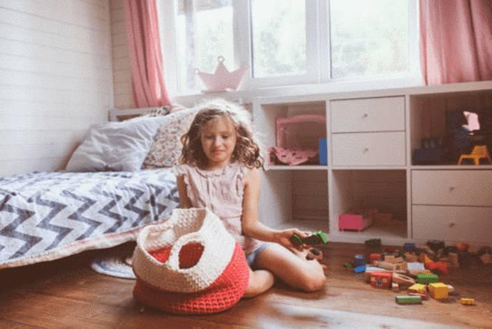 fille-assise-dans-sa-chambre-en-train-de-ranger-des-jouets-dans-un-sac