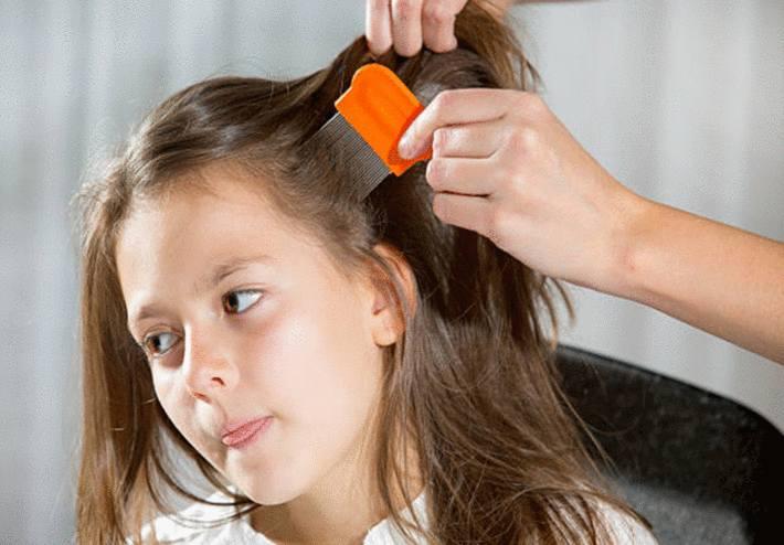 fille-brune-aux-cheveux-lisses-se-faisant-peigner-les-cheveux-avec-un-peigne-à-dents-serrées-métalliques