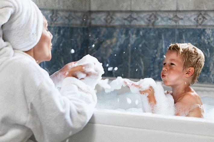 garçonnet-blond-soufflant-la-mousse-de-son-bain-vers-sa-maman