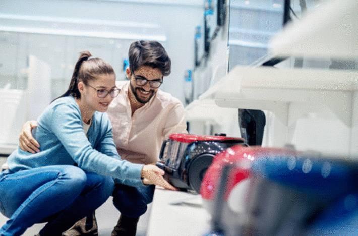 homme-brun-et-femme-brune-à-lunette-souriant-examinant-un-aspirateur-sans-sac-dans-une-rangée-d'-aspirateurs-sans-sac-en-magasin