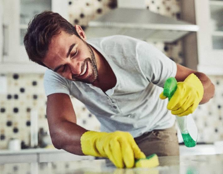 homme-brun-nettoyant-un-plan-de-travail-avec-une-éponge-végétale
