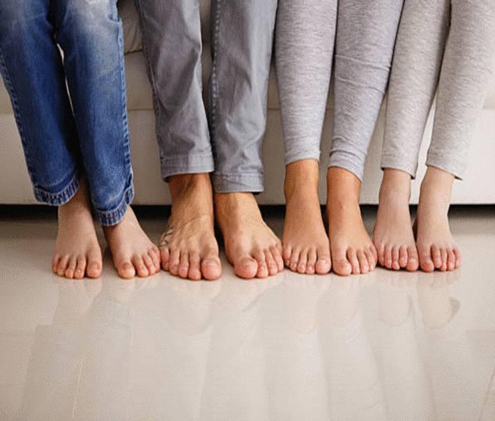 huit-pieds-nus-cote-à-cote-sur-du-carrelage-beige-brillant