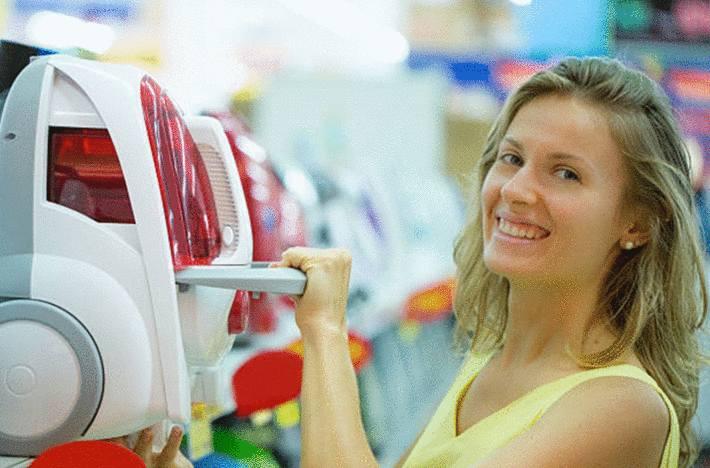jeune-femme-blonde-souriant-ayant-choisi-un-aspirateur-traîneau-dans-un-rayon-d'-aspirateurs-en-magasin