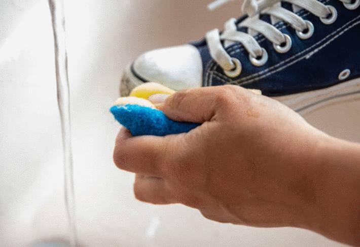 main-avec-une-éponge-propre-frottant-une-chaussure-en-toile
