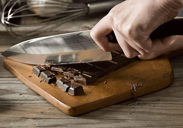 main-coupant-une-tablette-de-chocolat-avec-un-couteau-à-lame-large