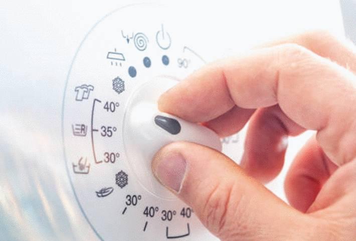 main-d-homme-tournant-le-bouton-de-température-du-lave-linge