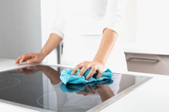 main-passant-le-chiffon-en-microfibres-sur-la-plaque-vitrocéramique-nettoyée-au-vinaigre