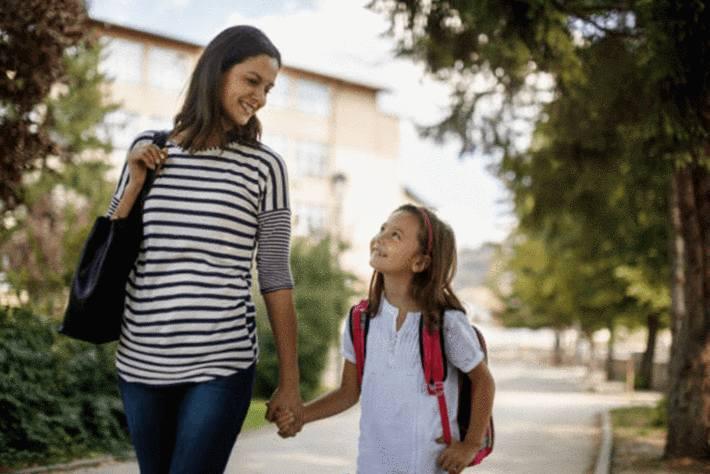 maman-et-fille-se-tenant-la-main--en-souriant-sur-le-chemin-de-l-école