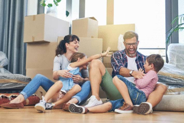 parents-chatouillant-leurs-deux-enfants-assis-devant-les-cartons-de-déménagement