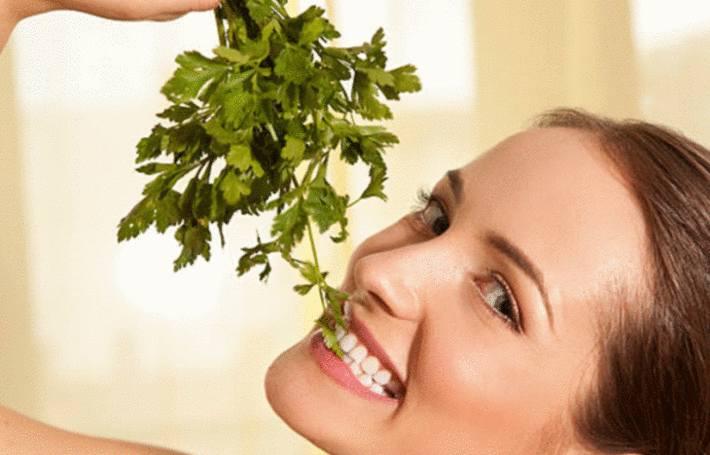 une femme mange du persil, bon pour la santé
