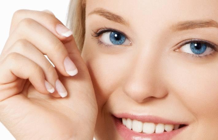 une jeune femme souriante montre ses beaux ongles blancs